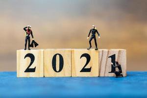 miniatyrdykare dyker runt träklossar med nummer 2021, gott nytt årskoncept foto