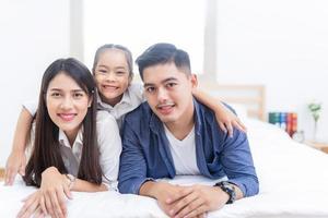 lycklig familj som ligger på en säng foto