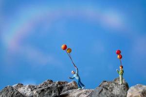 miniatyrfamilj som håller ballonger på en sten med en blå himmelbakgrund