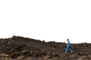 miniatyr man kör på marken isolerad på en vit bakgrund, kör för hälsa koncept foto
