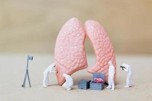 miniatyrforskare som observerar och diskuterar konceptet för mänskliga lungor, virus och bakterieinfektion foto