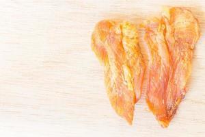 torkad kyckling ryckig för hundar på en träbakgrund foto