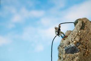 miniatyrvandrare som klättrar upp på ett klipp-, sport- och fritidskoncept foto