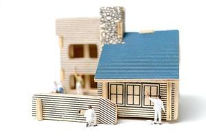 miniatyrmålare som målar ett trähus på en vit bakgrund foto