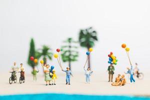 miniatyr människor njuter av sommarsemester på stranden foto
