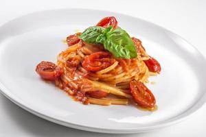 tallrik med spagetti med tomat och basilika foto
