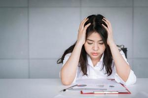 asiatisk affärskvinna som känner sig trött och stressad foto
