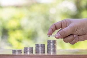 handen på investerare som håller mynt på mynt foto