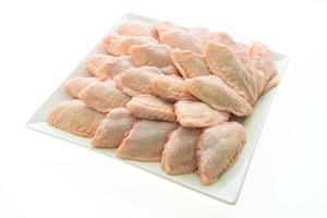 rå kycklingvingar på den vita plattan foto