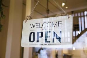 välkommen öppet tecken på en dörr foto