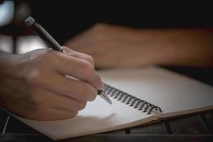 hand som håller en penna på en anteckningsbok foto