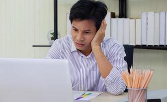 ung affärsman stressad på jobbet foto