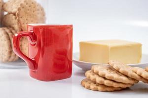 rött kaffemugg med kakor på vit bakgrund foto