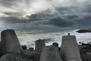 havsutsikt med enorma stenar och en våg foto