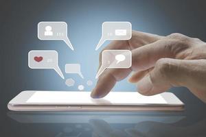 närbild av personens finger med hjälp av sociala medier chatt på en mobiltelefon foto