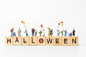 miniatyrfolk som håller ballonger med träklossar med text halloween på en vit bakgrund foto