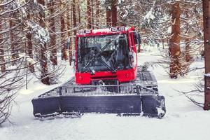 snöskoter för att justera spåren för längdskidåkare i vinterskogen foto