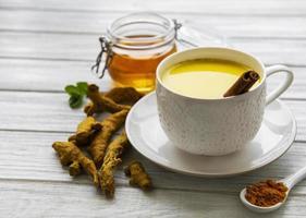 gyllene mjölk med kanel, gurkmeja, ingefära och honung över vit trä bakgrund foto