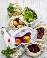 färska frukter och grönsaker i eco bomullspåsar på bordet i köket foto