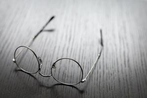 trådramglasögon som ligger upp och ner på ett träbord foto