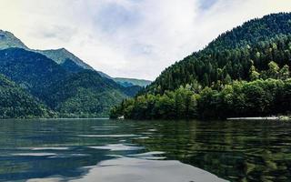 landskap med sjön ritsa och berg med en molnig blå himmel foto
