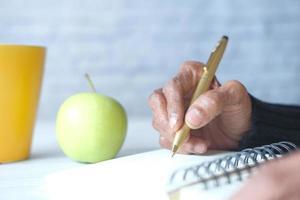 närbild av äldre kvinnas handstil på anteckningsblocket