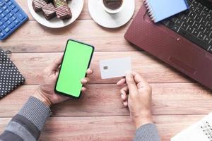 hand som håller kreditkort och använder smart telefon som handlar online foto