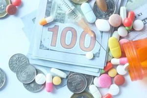 hälsokostnadskoncept med piller och kontanter på bordet foto