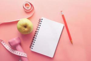 fitness koncept med hantel, äpple och anteckningsblock på rosa bakgrund