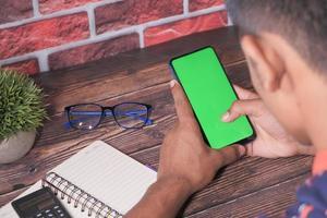 bakifrån av ung man använder smart telefon inomhus