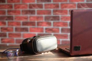 vr glasögon och bärbar dator på bordet foto