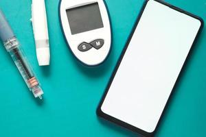 diabetiska mätverktyg, insulin och smart telefon på blå bakgrund foto