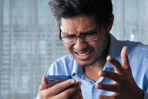 upprörd man använder smart telefon