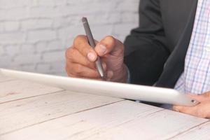 affärsman som använder den digitala minnestavlan på kontorsskrivbordet