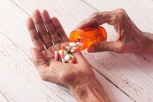äldre kvinnahänder tar medicin, närbild foto