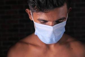 ung man med skyddande ansiktsmask isolerad på svart bakgrund
