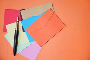 färgglatt kuvert på orange bakgrund med kopieringsutrymme foto