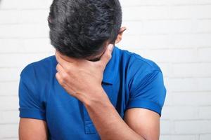 närbild av ledsen man som täcker ansiktet med handen foto