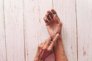 äldre kvinna som lider av ledvärk foto
