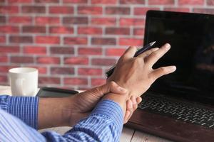 ung man i lidande smärta i handleden, närbild foto