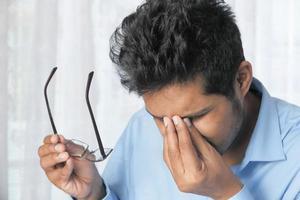 närbild av upprörd man som lider av ögonsmärta