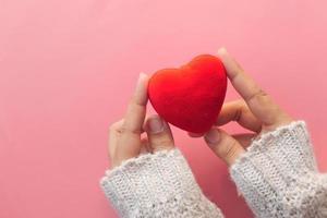 kvinnas hand som rymmer rött hjärta på rosa bakgrund foto