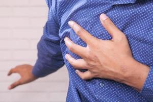 ung man håller bröstet i smärta