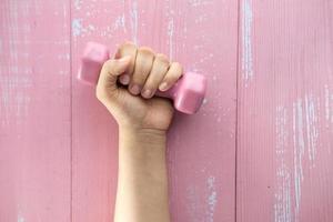 närbild av kvinnans hand som håller den rosa hanteln
