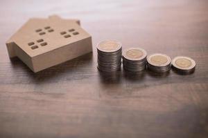 liten trähusmodell på bordet med mynt foto