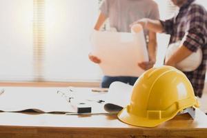konstruktionsskyddshjälmar på bordet med ingenjör som håller ritningsbakgrund foto