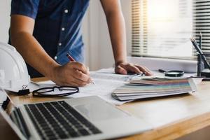 kreativ designer kontrollerar och skriver på papper på bordet foto