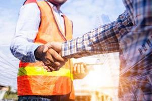 arkitektentreprenör som skakar hand med klienten på byggarbetsplatsen foto