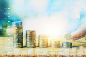 finansiera med pengar staplade med mynt och diagram, dubbel exponering med stad foto