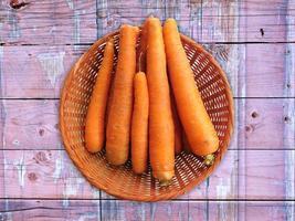 morötter i en flätad korg på en träbordbakgrund foto
